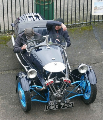 A parked Morgan three-wheeler with two exposed but well wrapped occupants.