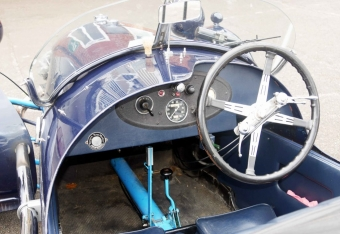 The cockpit of a pre-war three-wheeler, showing the sparse instrumentation and various levers on the steering wheel.